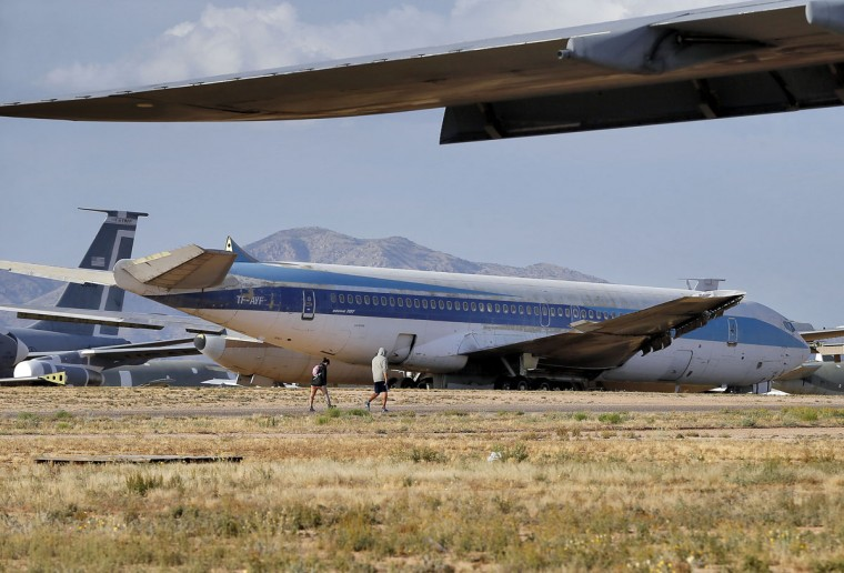 309th Aerospace Maintenance and Regeneration Group employees walk past a Boeing 707 jet at the boneyard, Thursday, May 14, 2015 at Davis-Monthan Air Force Base in Tucson, Ariz. (AP Photo/Matt York)