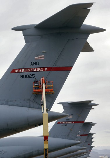 Workers apply rudder locks on a Lockheed C-5 Galaxy cargo jet at the 309th Aerospace Maintenance and Regeneration Group boneyard Friday, May 15, 2015 at Davis-Monthan Air Force Base in Tucson, Ariz. The C-5 has been used to support US military operations in all major conflicts since 1969 including Vietnam, Iraq, Yugoslavia and Afghanistan. (AP Photo/Matt York)