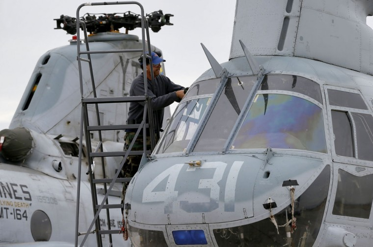 A crew member from from the 309th Aerospace Maintenance and Regeneration Group boneyard applies tape to seams on a Boeing Vertol CH-46 Sea Knight in preparation for storage after it's arrival, Friday, May 15, 2015 at Davis-Monthan Air Force Base in Tucson, Ariz. (AP Photo/Matt York)