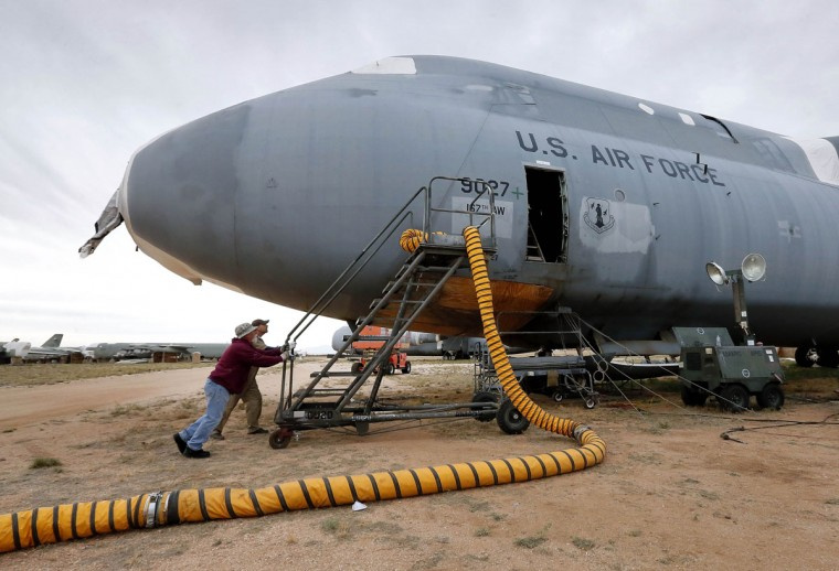 Workers prepare to reclaim parts from a Lockheed C-5 Galaxy cargo jet at the 309th Aerospace Maintenance and Regeneration Group boneyard Friday, May 15, 2015 at Davis-Monthan Air Force Base in Tucson, Ariz. Some aircraft at the boneyard are reclaimed to keep existing fleets in service. (AP Photo/Matt York)