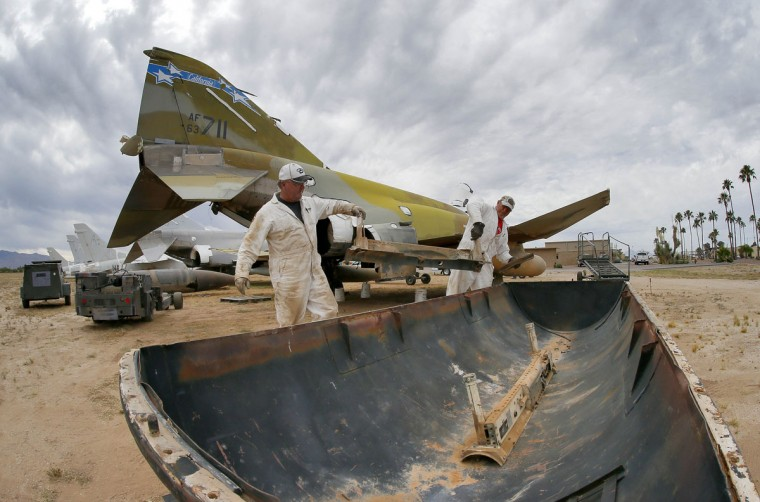Phil Kovaric and Dennis Varney remove the missile rails from an F-4 Phantom slated for destruction at the 309th Aerospace Maintenance and Regeneration Group boneyard in Tucson, Ariz. on Thursday, May 21, 2015. The 309th is the United States Air Forceís aircraft and missile storage and maintenance facility and provides long and short-term aircraft storage, parts reclamation and disposal. (AP Photo/Matt York)