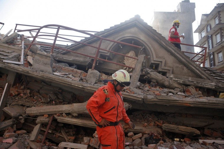 A Mexican rescue worker stands at the site of a building that collapsed in an earthquake in Kathmandu, Nepal, Tuesday, May 12, 2015. A major earthquake has hit Nepal near the Chinese border between the capital of Kathmandu and Mount Everest less than three weeks after the country was devastated by a quake. (AP Photo/Niranjan Shrestha)