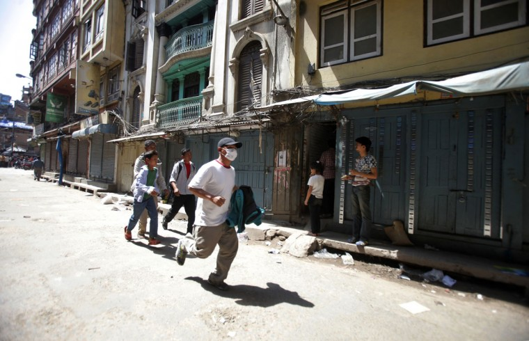 A Nepalese man runs to safety after a second earthquake hit Nepal in Kathmandu, Nepal, Tuesday, May 12, 2015. A major earthquake hit a remote mountainous region of Nepal on Tuesday, triggering landslides and toppling buildings less than three weeks after the country was ravaged by another deadly quake. (AP Photo/Bikram Rai)