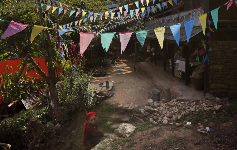 In this photo taken on Saturday, May 2, 2015, prayer flags line the entrance to Tika Devi Khanal, 81, damaged home in the destroyed village of Pokharidanda, near the epicenter of the April 25 massive earthquake, in the Gorkha District of Nepal. (AP Photo/Wally Santana)