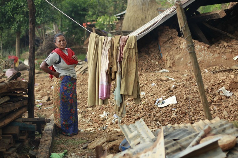 In this photo taken on Saturday, May 2, 2015, standing in the rubble of her home, Radha Shrestha, 42, strings a clothesline to hang laundry in the destroyed village of Pokharidanda, near the epicenter of the April 25 massive earthquake, in the Gorkha District of Nepal. (AP Photo/Wally Santana)