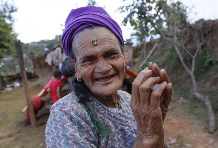 In this photo taken on Saturday, May 2, 2015, Loysyanri Khanal, 78, smiles outside of her home in the destroyed village of Pokharidanda, near the epicenter of the April 25 massive earthquake, in the Gorkha District of Nepal. (AP Photo/Wally Santana)