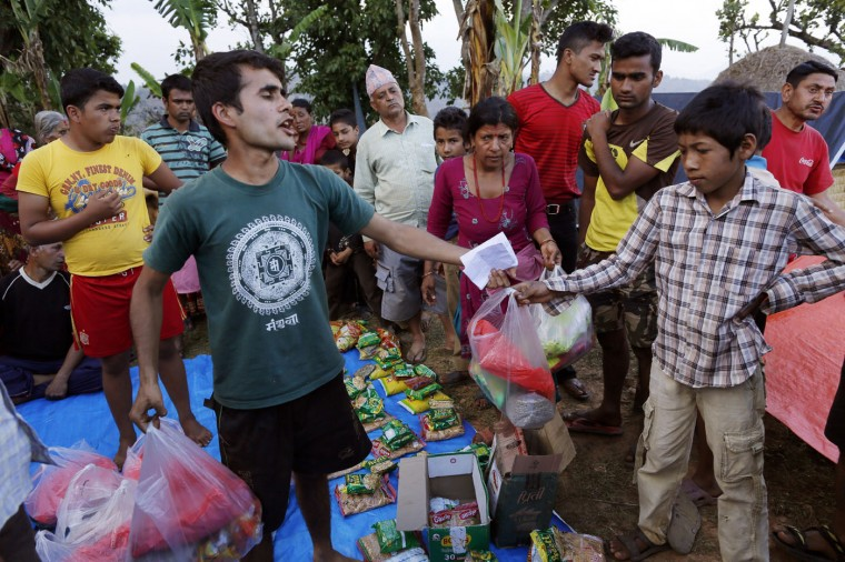 In this photo taken on Saturday, May 2, 2015, Rajendra Khanal, 21, shouts out names as he distributes aid packets to families in the destroyed village of Pokharidanda, near the epicenter of the April 25 massive earthquake, in the Gorkha District of Nepal. (AP Photo/Wally Santana)