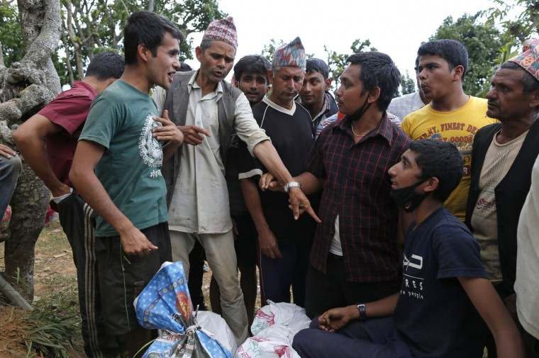 In this photo taken on Saturday, May 2, 2015, Rajendra Khanal, 21, left, resolves a dispute over aid in the destroyed village of Pokharidanda, near the epicenter of the April 25 massive earthquake, in the Gorkha District of Nepal. (AP Photo/Wally Santana)