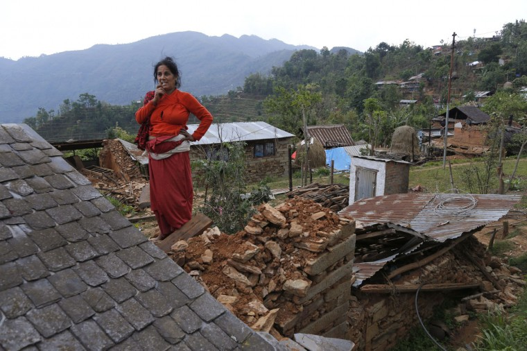 In this photo taken on Saturday, May 2, 2015, Lila Khanal gazes over the rubble of her collapsed home in the destroyed village of Pokharidanda, near the epicenter of the April 25 massive earthquake, in the Gorkha District of Nepal. (AP Photo/Wally Santana)