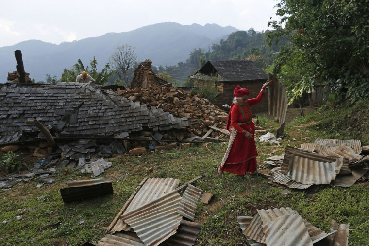 In this photo taken on Saturday, May 2, 2015, Prem Kumari Khanal, 68, piles corrugated sheets of tin in the destroyed village of Pokharidanda, near the epicenter of the April 25 massive earthquake, in the Gorkha District of Nepal. (AP Photo/Wally Santana)