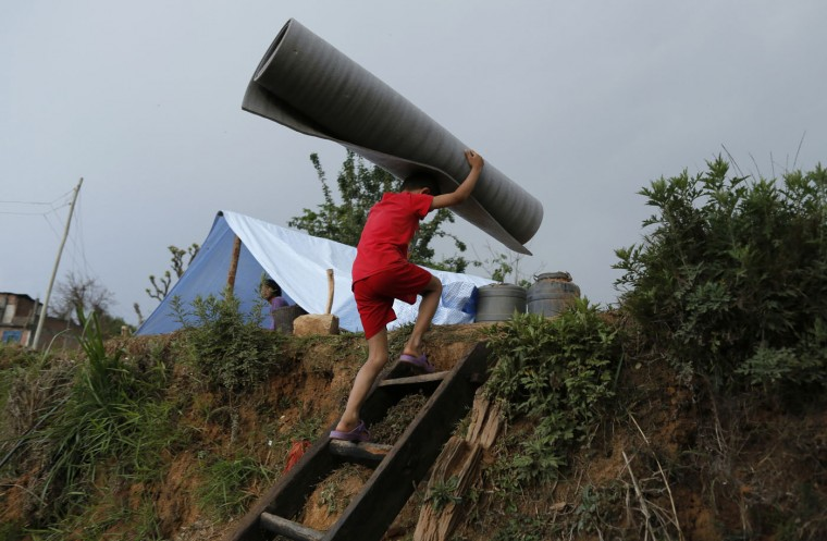 In this photo taken on Saturday, May 2, 2015, a young boy carries a foam bedroll up a set of stairs in the destroyed village of Pokharidanda, near the epicenter of the April 25 massive earthquake, in the Gorkha District of Nepal. People in villages reachable by road in Nepalís quake-wracked central Gorkha District are fending for themselves, with the government so short on relief theyíve been forced to focus only on far-flung reaches of the remote Himalayas. (AP Photo/Wally Santana)