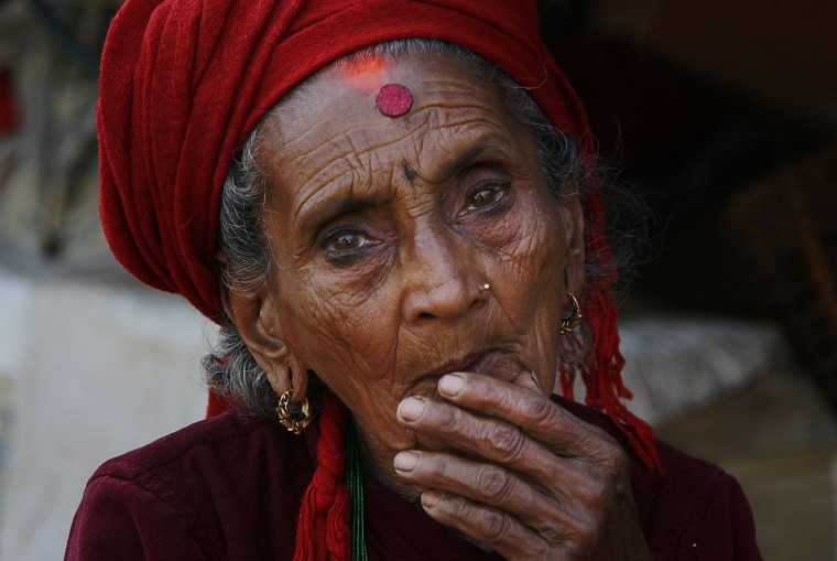 In this photo taken on Saturday, May 2, 2015, Tika Devi Khanal, 81, sits at her damaged home in the destroyed village of Pokharidanda, near the epicenter of the April 25 massive earthquake, in the Gorkha District of Nepal. (AP Photo/Wally Santana)