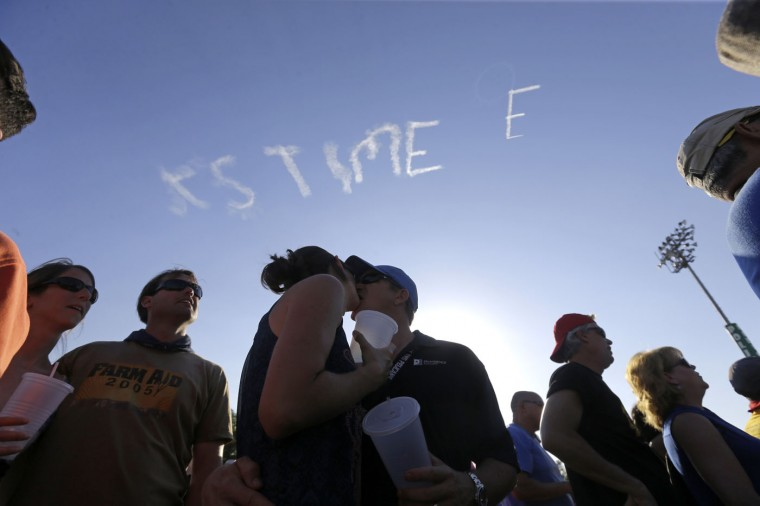 In this May 1, 2015 photo, Kevin Mueller, of Austin, Texas, kisses his wife Erin Mueller, as skywriter Nathan Hammond writes messages of hope and love over New Orleans, during the New Orleans Jazz & Heritage Festival. (AP Photo/Gerald Herbert)