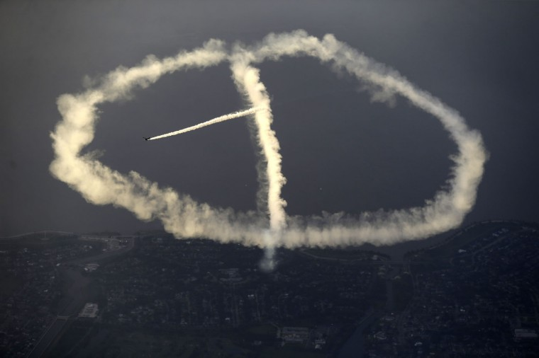 In this May 2, 2015 photo, skywriter Nathan Hammond works on a peace sign as he writes messages of hope and love over New Orleans, during the New Orleans Jazz & Heritage Festival. (AP Photo/Gerald Herbert)