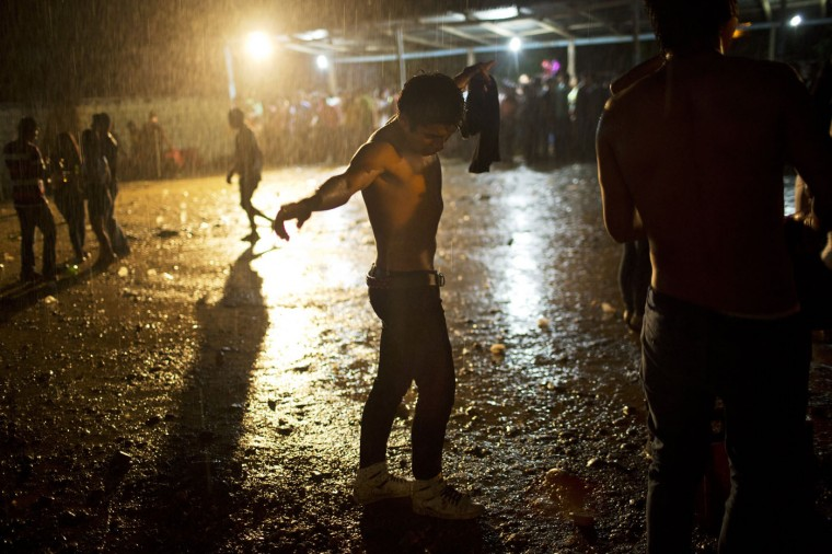 In this March 16, 2015 photo, a young man dances under a heavy rain during a concert by huayno singer Ely Corazon, in La Mar, province of Ayacucho, Peru. The average cocaine backpacker, or mochilero, is typically recruited by relatives and friends - often at festivities where liquor flows. They tend not to tell their parents, who nearly always disapprove. (AP Photo/Rodrigo Abd)