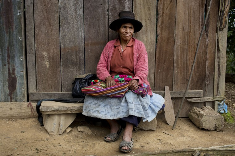 In this March 15, 2015 photo, Rufina Galvez chews coca leaves outside her house in La Mar, province of Ayacucho, Peru. Adored by her son Yuri, he would ferry her around Ayacucho on his blue motorcycle, buy her groceries, and make sure she always had cell phone minutes. A university student, Yuri had gotten his fatherís permission to haul coca to pay for his agronomy studies. In March 2013, he was found face-up on a mountain trail, with bullet wounds to his head, stomach and arm. (AP Photo/Rodrigo Abd)