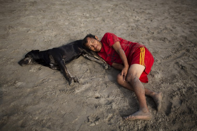 In this April 25, 2015 photo, a man and dog rest on Fishermen's Beach before a therapeutic swimming session in Lima, Peru. Along Lima's coast, people seek relief from the ailments doctors have been unable to cure. (AP Photo/Rodrigo Abd)