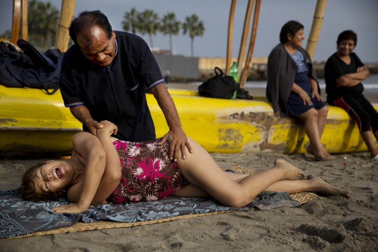 "In this May 15, 2015 photo, chiropractor Felix Retamoso treats Virginia Espinoza's lower back pain on Fishermen's Beach, where she took a therapeutic swim in the Pacific Ocean in Lima, Peru. ""He's not only cheaper, but we're outdoors in direct contact with nature,"" said the 67-year-old. (AP Photo/Rodrigo Abd)"
