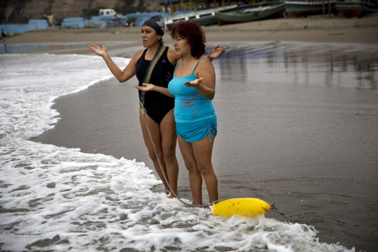 "In this May 8, 2015 photo, sisters Zoraida Infante, left, and Graciela Trujillo pray on Fishermen's Beach before therapeutic swimming in the Pacific Ocean in Lima, Peru. Under overcast skies, the bathers practice thalassotherapy, which derives from the Greek ""thalasso,"" for ""sea,"" and draws on the ocean's healing properties. (AP Photo/Rodrigo Abd)"