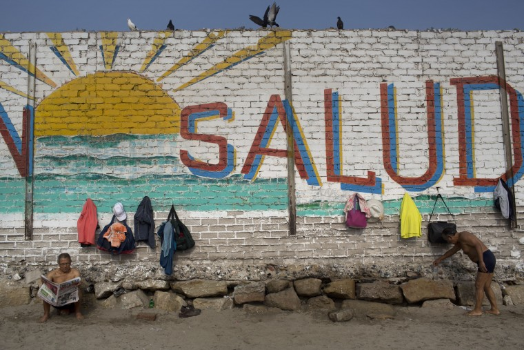 "In this April 25, 2015 photo, a man reads the paper next to a wall decorated with a sun and the Spanish word ""Health"" on Fishermen's Beach, where bathers come for therapeutic swimming in Lima, Peru. Some hug each other and go in as a group, jumping, laughing and running along the shore. Others bathe silently by themselves in the calm, gray sea water. (AP Photo/Rodrigo Abd)"