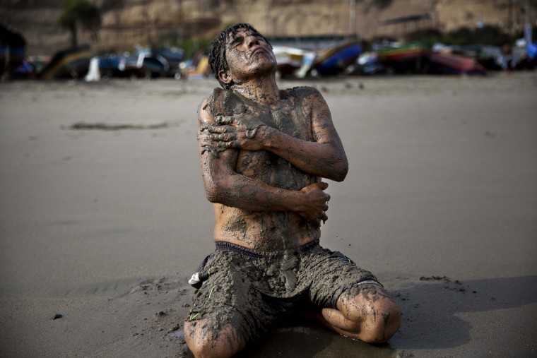 In this May 14, 2015 photo, Berto Nestaris covers his body with sand on Fishermen's Beach in Lima, Peru. Berto, a 55-year-old sociologist, said therapeutic massages using sea sand helps his circulation and nervous system. (AP Photo/Rodrigo Abd)