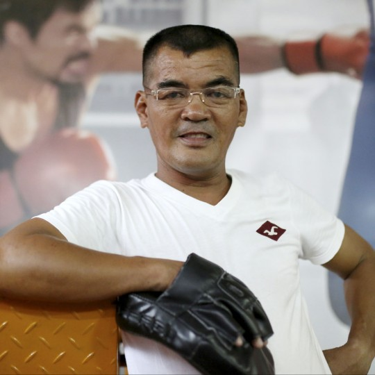 """In this April 21, 2015, photo, retired Filipino boxer and now trainer Melvin Magramo poses in front of a picture of Filipino boxing hero Manny Pacquiao inside their boxing gym in suburban Paranaque, south of Manila, Philippines. Magramo, 44, a former World Boxing Organization flyweight champion who lost to Pacquiao by decision in a 10-round, non-title fight in 1997, said, """"The number of our (boxing) students has been increasing along with the popularity of Pacquiao... It was God who put him where he is now."""" (AP Photo/Aaron Favila)"""