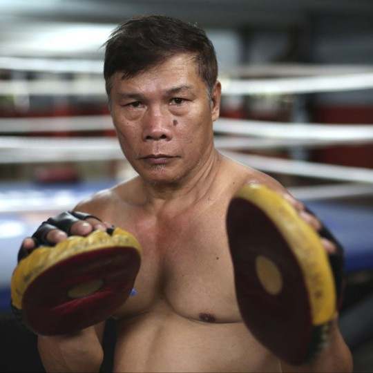"""In this April 21, 2015, photo, retired Filipino boxer and now trainer William Develos poses inside his boxing gym in suburban Paranaque, south of Manila, Philippines. Develos, 58, said, """"In training, you are already being made to suffer so that it will be easier for you when the time comes."""" (AP Photo/Aaron Favila)"""