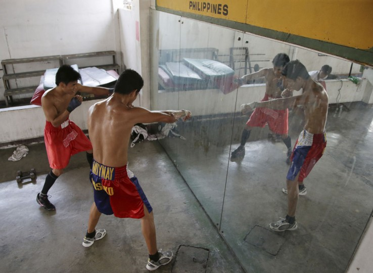 In this April 22, 2015, photo, Filipino boxer Rolly Macaso, left, and Joemarie Noynay practice in front of a mirror during their training at a boxing gym in suburban Paranaque, south of Manila, Philippines. (AP Photo/Aaron Favila)