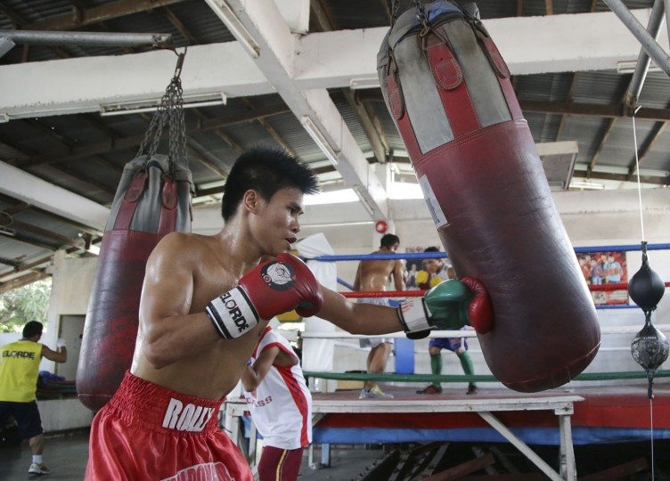 In this April 22, 2015, photo, Filipino boxer Rolly Macaso trains on a punching bag at a boxing gym in suburban Paranaque, south of Manila, Philippines. (AP Photo/Aaron Favila)