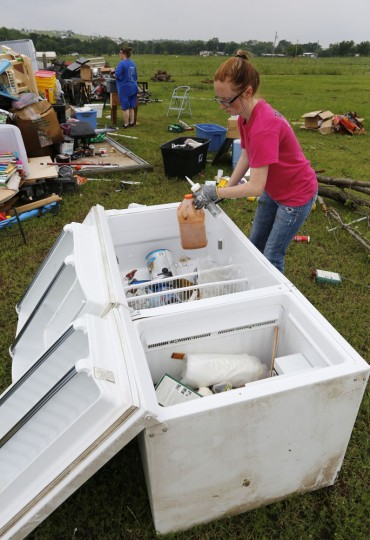 Sapphire Love uses a refrigerator as storage for recovered items as neighbors and friends help clean up after Thursday night's tornado passed the area on Friday, May 8, 2015 in New Fairview, Texas. Strong storms spawned several tornadoes and dumped heavy rain on North Texas overnight, flooding roads and damaging train tracks in an area where a freight train derailed before dawn on Friday, officials said. (David Kent/The Fort Worth Star-Telegram via AP)