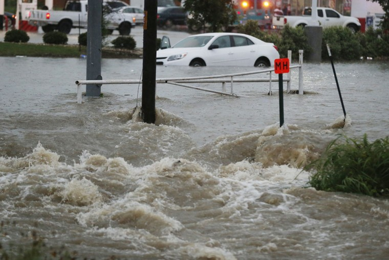 A motorist is rescued from a car trapped at a low spot near an intersection Monday, May 25, 2015 in Waco, Texas. Widespread flooding and trapped vehicles were reported throughout the area. (Rod Aydelotte/Waco Tribune Herald via AP)