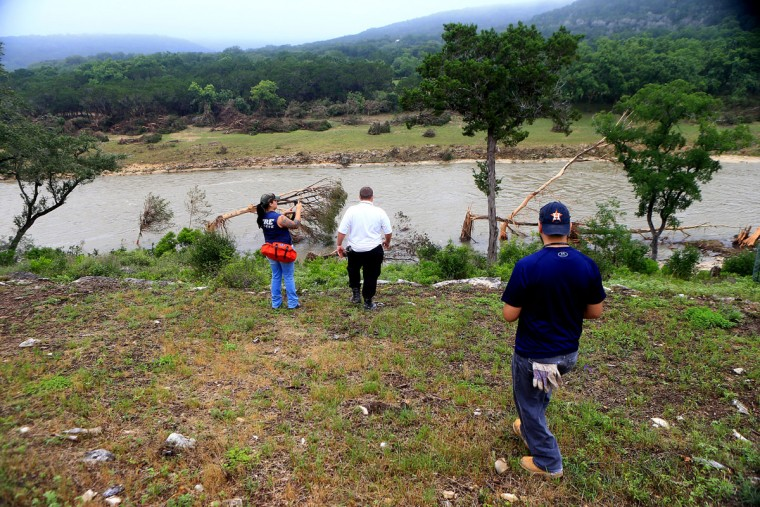 Members of the search and rescue team Alaena Tate, Robert Perkins and Matthew Marty Lopez view the Blanco River as they prepare to search for people who are missing after heavy flooding Wednesday, May 27, 2015, around Umphery Ranch located between Wimberley and San Marcos, Texas. The search went on for about a dozen people, including a group that disappeared after a vacation home was swept down a river and slammed into a bridge. (Gabe Hernandez/Corpus Christi Caller-Times via AP)
