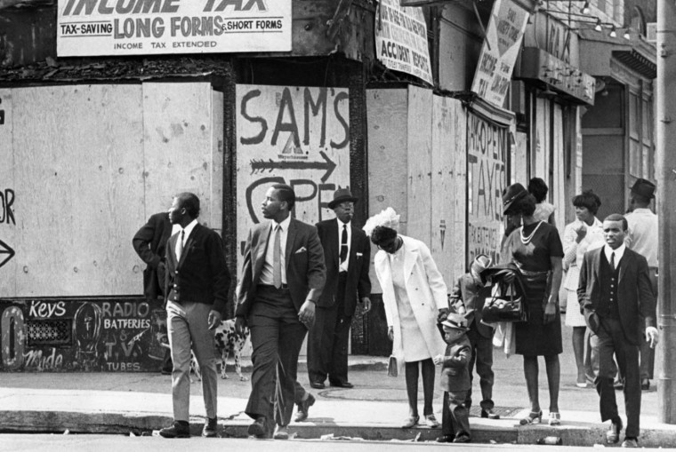 4/14/1968: Families walk along Pennsylvania Avenue, past burnt and boarded stores on Easter Sunday during the riots. (Weyman Swagger/Baltimore Sun)