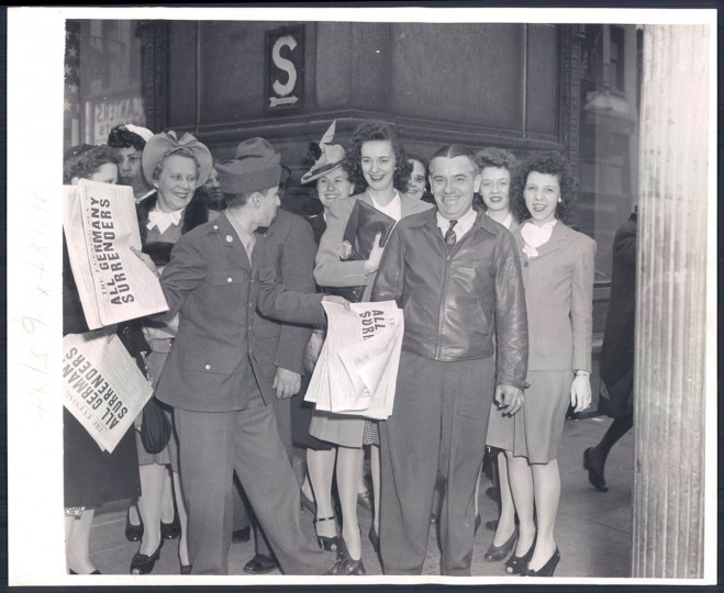 """Pvt. William Leon of New Cumberland, PA, on a fine day here jumps back into his old job of selling newspapers. Today's headline, """"ALL GERMANY SURRENDERS"""" (A. Aubrey Bodine/Baltimore Sun)"""