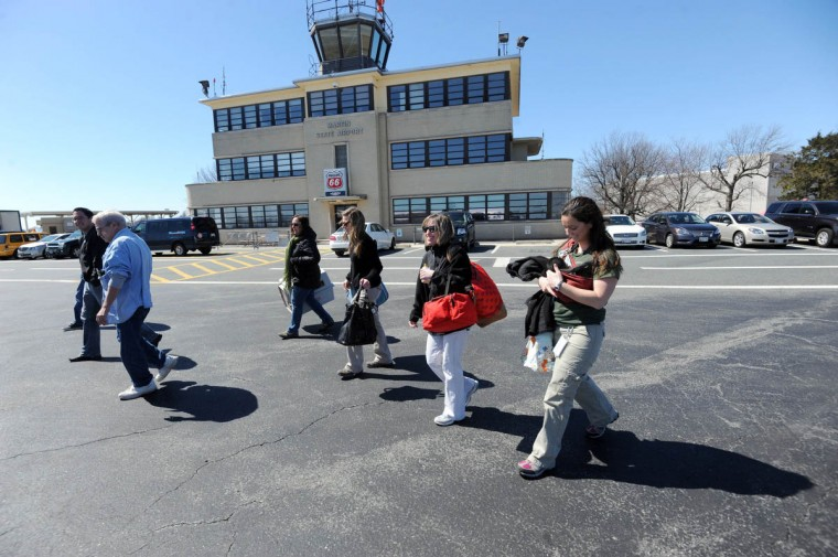 Second from right, Carey Ricciardone, mammal collection manager, and Claire MacNamara, Chimp Forest Area manager, holding Keeva, a chimpanzee born recently at the Maryland Zoo in Baltimore, walk toward a private plane at Martin State Airport. Third from left, Jeff Luizza, Old Forge, PA, will fly them to Tampa, Fl, were Keeva will be placed with a surrogate chimpanzee at Tampa's Lowry Park Zoo. (Kim Hairston/The Baltimore Sun)