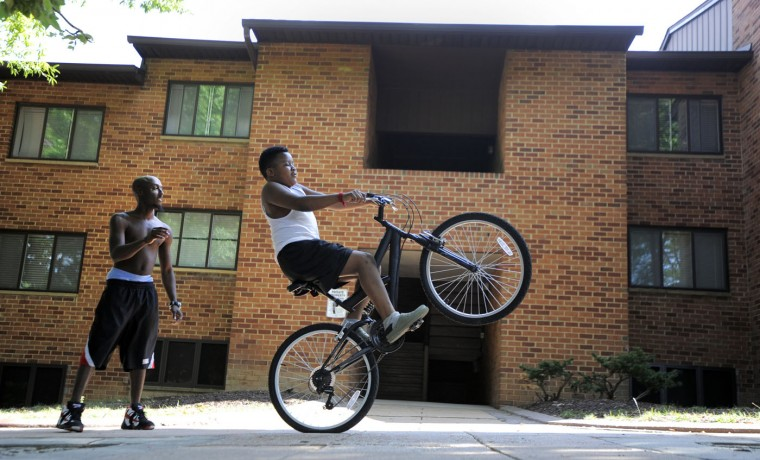8/15/14: Daniel Griffin, 28 and Micah Guess, 9, enjoy an afternoon at the Orchard Garden apartments during the Druid Heights back-to-school rally. (Lloyd Fox/Sun Photographer)