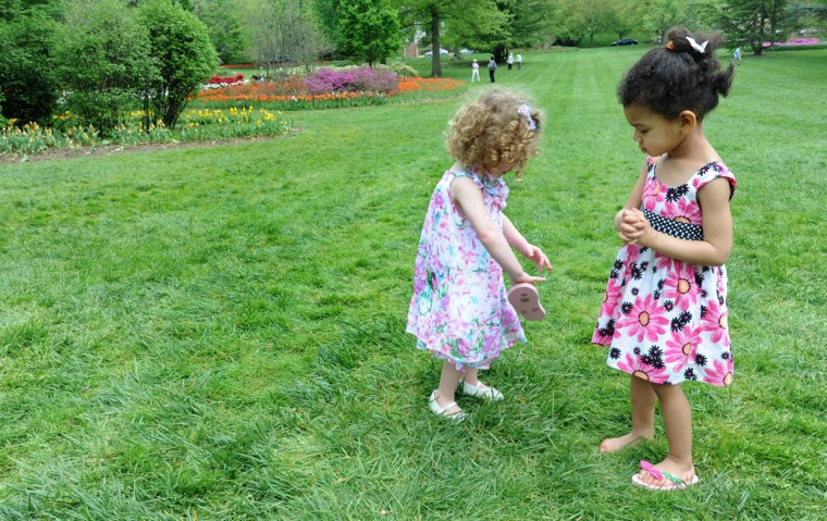 Alexa Lyons, 3, left, brings a missing flip-flop to her sister Juliet Novack, almost three, as they play among the blooming flowers and trees at Sherwood Gardens. (Algerina Perna/Baltimore Sun)