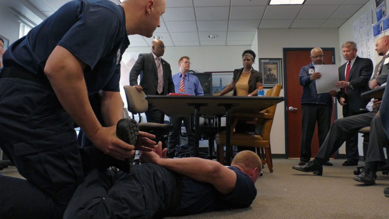 """Addressing the group of investigators, Dr. David L. Higgins, MD, P.C. looks at an enlargement of a frame from a cellphone video with Baltimore Police Major Stanley Brandford while police training instructors (left) mimic the position known as a """"leg lace"""" in which Freddie Gray was when he was placed under arrest after watching a cellphone video of the arrest, during a meeting inside the Professional Standards & Accountability Bureau of the Deputy Commissioner's Office, where investigators review and continue their internal investigation at department headquarters. Karl Merton Ferron/Baltimore Sun"""