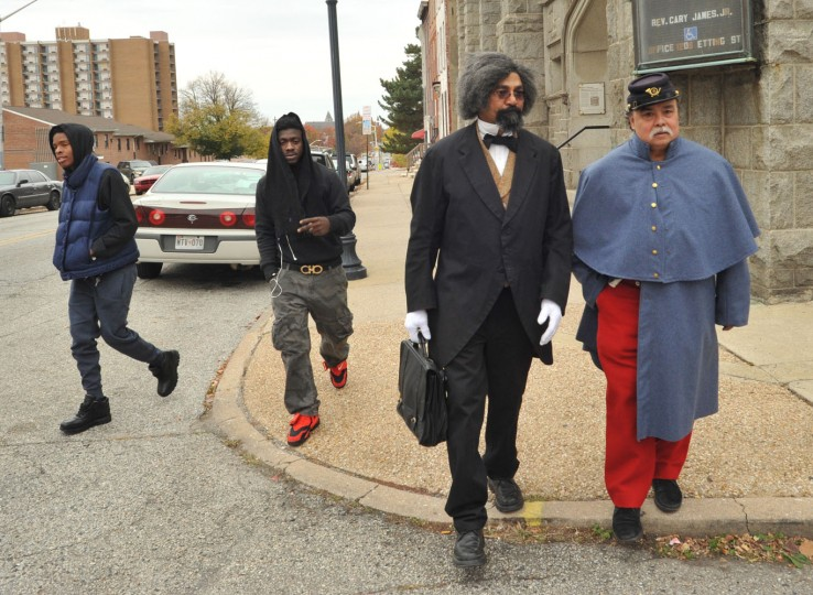 "11/16/14: ""Frederick Douglass,"" second from right, played by Steven A. Cole, leaves the Sharp Street Memorial United Methodist Church on Etting Street with Robert Reyes, right, the vice-president of the Baltimore Civil War Museum, which sponsored Cole's visit to Baltimore. Cole, of Freeport, Illinois, re-enacted the ""A Friendly Word to Maryland"" speech given by Douglass 150 years ago at the original Sharp Street Church following the emancipation of slaves in Maryland. He also spoke to the Urban League at the Orchard Street Church on Saturday, and visited other historic sites. The Nov. 17, 1864 speech given by Douglass at the Sharp Street Church marked the abolitionist's first return to Maryland in 26 years. (Amy Davis / Baltimore Sun)"