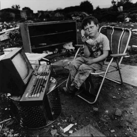 "A little boy creates his own fantasy game amid his junky surroundings, in this photograph by Mary Ellen Mark, ""Paddy Joyce. Travelers Encampment at Funglas, Ireland, 1991."" (AP Photo/Kreisberg Group Ltd. /Mary Ellen Mark)"