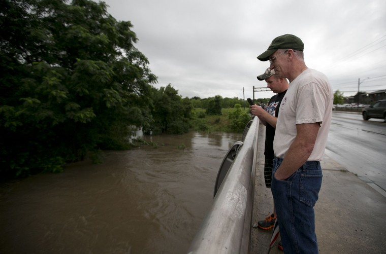 Kyle and Mark Ziegler look down at the rushing waters of Williamson Creek from the South 1st Street bridge on Monday, May 25, 2015, in Austin, Texas. (Deborah Cannon/Austin-American Statesman/TNS)