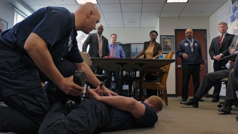 """Addressing the group of investigators, Dr. David L. Higgins, MD, P.C. gives his opinion about injuries or blood flow to the lower extremities at the position demonstrated by police training instructors (left) while Baltimore Police Major Stanley Brandford (standing next to Higgins) as the instructors attempt to mimic the position known as a """"leg lace"""" in which Freddie Gray was when he was placed under arrest after watching a cellphone video of the arrest, during a meeting inside the Professional Standards & Accountability Bureau of the Deputy Commissioner's Office, where investigators review and continue their internal investigation at department headquarters. Karl Merton Ferron/Baltimore Sun"""