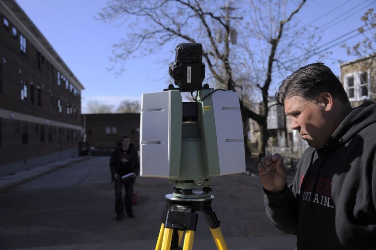 Detective Timothy Hamilton prepares sophisticated image-gathering equipment to scan the terrain and its contents on Bruce Court behind Gilmor Homes at Presbury Street, to gain a 360-degree, 3-D high-resolution visual of the area as Baltimore Police scour the area to dig up any clues or evidence while investigating the death of resident Freddie Gray, 25, after he was taken into police custody. Karl Merton Ferron/Baltimore Sun