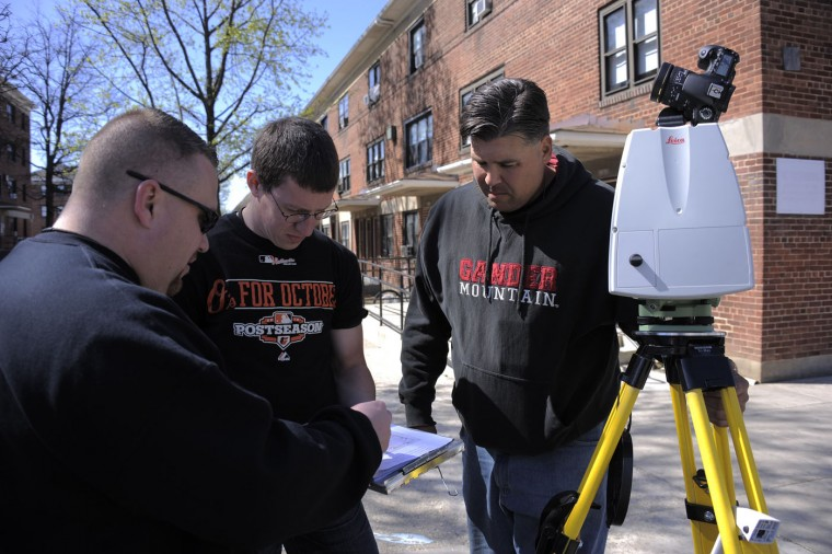 Standing at Gilmor Homes, (from left) Baltimore Police Detective Michael Boyd, crime lab recording technician Thomas Wizman and DetectiveTimothy Hamilton check logs of sophisticated image-gathering equipment which scans the terrain and its contents to gain a 360-degree, high-resolution visual of the area, look on a map in order to scan the route where a police transport van had allegedly taken, as Baltimore Police scour the area to dig up any clues or evidence while investigating the death of resident Freddie Gray, 25. Karl Merton Ferron/Baltimore Sun
