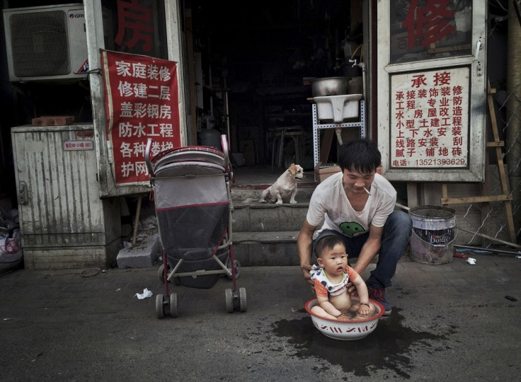 A Chinese man washes his young son in a bowl in the street in a residential neighborhood on May 27, 2015 in Beijing, China. (Photo by Kevin Frayer/Getty Images)