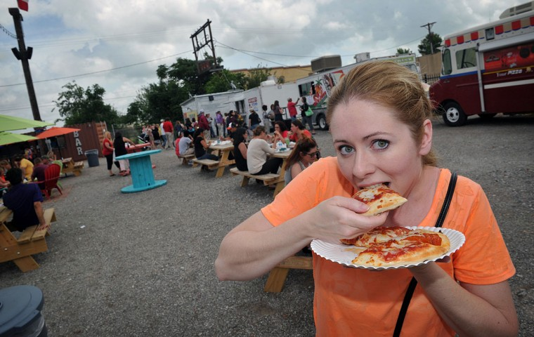 Tara Henry eats a slice of Stone Oven Pizza, Thursday, May 28, 2015, at The Yard, a new food truck park in downtown Wichita Falls, Texas. The Yard is part of a movement of food trucks and trailers featuring interesting cuisine. Live music will be featured on Saturdays and Sundays. (Torin Halsey/Times Record News via AP)