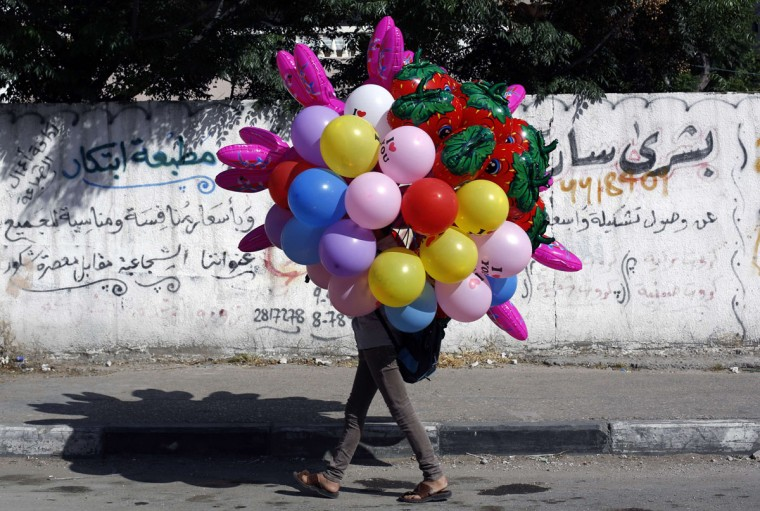 A Palestinian street vendor carries balloons on a street on May 14, 2015 in Gaza City. (AFP Photo/Mohammed Abed)