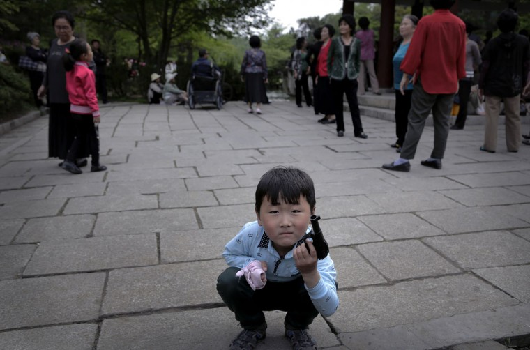 A North Korean boy plays with a toy pistol as people gather around a gazebo at the Moranbong (Moran Hill) in Pyongyang, North Korea on Sunday, May 3, 2015. (AP Photo/Wong Maye-E)