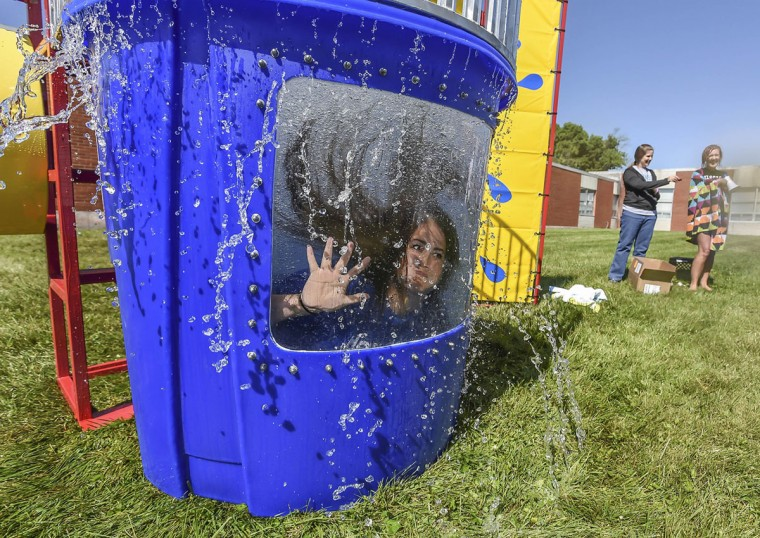 "Instructor Jennifer Fowler waves to students after getting dunked Friday, May 22, 2015., behind Junction City Elementary School in Junction City, KY. Students earned tickets all year for demonstrating one of the 7 Habits. Each month a leader (ticket) was drawn out for a leader of the month for each class. Those students received a shirt and a treat. If you ticket was not drawn out it was placed in a container in the front office. Those tickets were used in our drawing for students to be picked for the dunk tank. We call it ""Dunk Mrs. Shunk"". (Clay Jackson/The Advocate-Messenger via AP)"