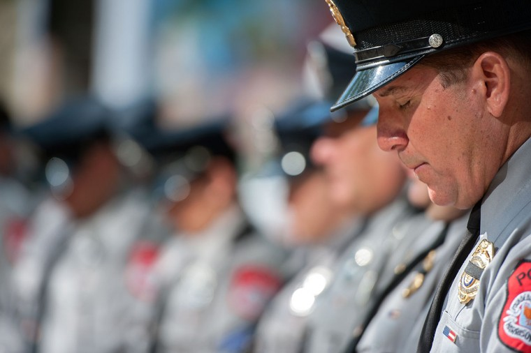 Harrisonburg Police Department Sgt. Pete Ritchie, Jr., bows his head in prayer during the National Police Week Flag Ceremony at the Public Safety building in downtown Harrisonburg, Va., Monday morning May 11, 2015. (Nikki Fox/Daily News-Record via AP)